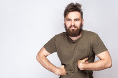 Portrait of funny crazy bearded man with dark green t shirt against light gray background. Royalty Free Stock Image