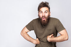 Portrait of funny crazy bearded man with tongue out and dark green t shirt against light gray background. Royalty Free Stock Photos