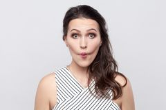 Portrait of funny crazy beautiful young brunette woman with makeup and striped dress standing and looking at camera with big eyes royalty free stock photos