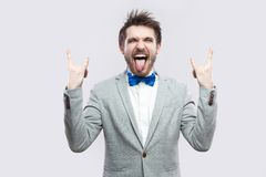 Portrait of funny crazy handsome bearded man in casual grey suit and blue bow tie standing with rock gesture, closed eyes and. Tongue out. indoor studio shot stock images