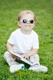 Portrait of funny cute adorable smiling laughing white Caucasian toddler child boy with blond hair in white t-shirt and sunglasses. Sitting on green grass Stock Photography