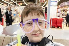 Portrait of funny cute boy wearing strange glasses made of fluorescent neon tubes, shopping mall stock photography