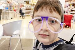 Portrait of funny cute boy wearing strange glasses made of fluorescent neon tubes, shopping mall stock image