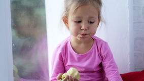 Portrait of funny cute little girl sitting on window sill and eating apple. Baby sitting on a window sill at day time and eating fruit with comical facial stock video