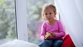Portrait of funny cute little girl sitting on window sill and eating apple. Baby sitting on a window sill at day time and eating fruit with comical facial stock footage