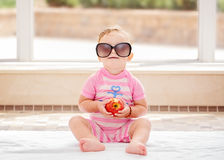 Portrait of funny cute white Caucasian smiling baby girl wearing large sunglasses sitting on floor in swimming pool Stock Images