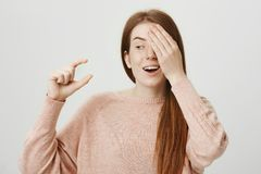 Portrait of funny emotive ginger girl covering one eye while showing something small or tiny with gesture and being. Amazed about it, standing against gray Stock Photography