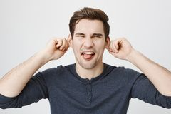 Portrait of funny european male model fooling around, stretching ears with hands and sticking out tongue while squinting. And standing over gray background Royalty Free Stock Photo