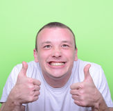 Portrait of with funny expression holding thumbs up against gree. This image is made in studio with model standing against colored backgrounds.Set of various Stock Photos