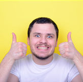 Portrait of with funny expression holding thumbs up against yell Stock Image