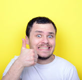 Portrait of with funny expression holding thumbs up against yell Royalty Free Stock Photos