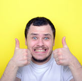Portrait of with funny expression holding thumbs up against yell Royalty Free Stock Images