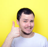 Portrait of with funny expression holding thumbs up against yell Royalty Free Stock Image