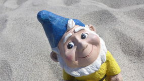Portrait of a funny garden gnome in front of the beach Royalty Free Stock Photography