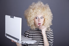 Portrait of funny girl in blonde wig with laptop. Royalty Free Stock Photo