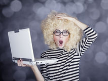 Portrait of funny girl in blonde wig with laptop. Studio shot. Royalty Free Stock Images