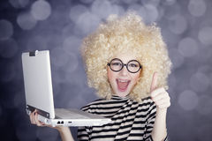 Portrait of funny girl in blonde wig with laptop. Stock Photo