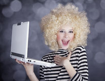 Portrait of funny girl in blonde wig with laptop. Stock Image