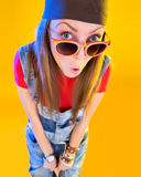 Portrait of funny girl in glasses and a brown hat. Stares at the viewer. Isolation on a yellow background stock photo