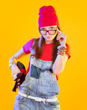 Portrait of funny girl in glasses and red caps. Seriously looking at viewer. Isolation on a yellow background stock photos