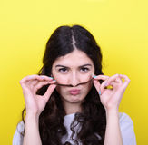 Portrait of funny girl making moustache against yellow backgroun Stock Image