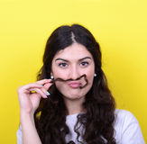 Portrait of funny girl making moustache against yellow backgroun Stock Images