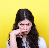 Portrait of funny girl making moustache against yellow backgroun Stock Photography