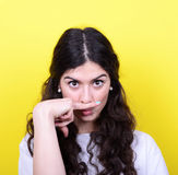 Portrait of funny girl making moustache against yellow backgroun Royalty Free Stock Photography