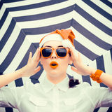 Portrait of a funny girl in Santa Claus hat and sunglasses. With bright painted lips next to a striped background stock photography