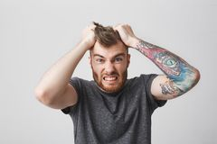 Portrait of funny good-looking bearded caucasian man with tattoo on left arm and stylish hairstyle holding hair with. Hands with and expression. Guy being angry stock images