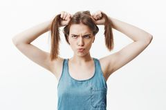 Portrait of funny handsome charming european girl with dark straight hair mowing eyes, holding hair with both hands Royalty Free Stock Photo