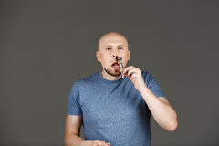 Portrait of funny handsome middle-aged man in grey shirt shaving over dark background. Stock Photos