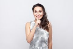 Portrait of funny happy beautiful young brunette woman with makeup and striped dress standing, smiling and looking at camera with stock image