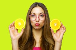 Portrait of funny happy girl holding halves of orange near face stock photography