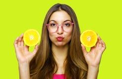 Portrait of funny happy girl holding halves of orange near face.  stock photography