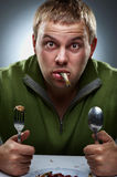 Portrait of funny hungry man. With fish in mouth Royalty Free Stock Photography