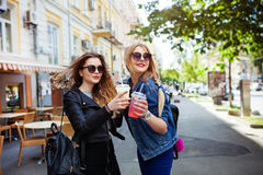 Portrait funny joyful attractive young women with drinks having fun on sunny street in city, smiling, lovely moments, best friends Royalty Free Stock Images