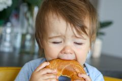 Portrait of funny little baby boy eating big bagel with closed eyes, fun face expression. Close-up, teething child royalty free stock photo