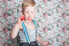 Portrait of funny little boy blowing soap bubbles  ( Portrait of funny little boy blowing soap bubbles. Background: floral, soft,. Portrait of funny little boy Stock Image