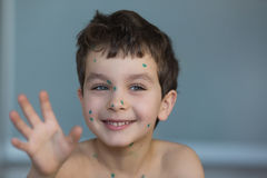 Portrait of a funny little boy with a green points. On a face Stock Image