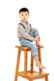 Portrait of a funny little boy sitting barefoot on a high stool. Isolated on white background Royalty Free Stock Photo
