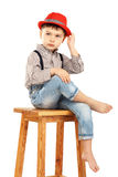 Portrait of a funny little boy sitting on a high stool in a red Royalty Free Stock Photo