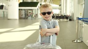 Portrait of a little boy in sunglasses with a suitcase at the airport. Portrait of a funny little boy in sunglasses and a gray t-shirt with a suitcase at the stock video