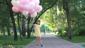 Portrait of funny little girl with balloons. Children run through the Park with a huge bunch of colorful balloons. two little girls with balloons on a background stock video