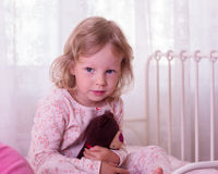 Portrait of a funny little girl in bed with toy. Royalty Free Stock Photo