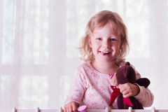 Portrait of a funny little girl in bed with toy. Royalty Free Stock Photography