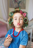 Portrait of funny little girl with a curlers does duck lips Royalty Free Stock Photos