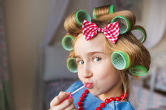 Portrait of funny little girl with a curlers and lipstick at hand and does duck lips Stock Photography