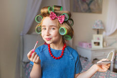 Portrait of funny little girl with a curlers paints lips and smiles in bedroom royalty free stock photo