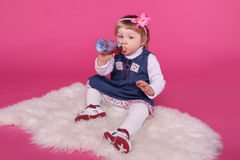 Portrait of funny little girl drinking water sitting on fur over Royalty Free Stock Image